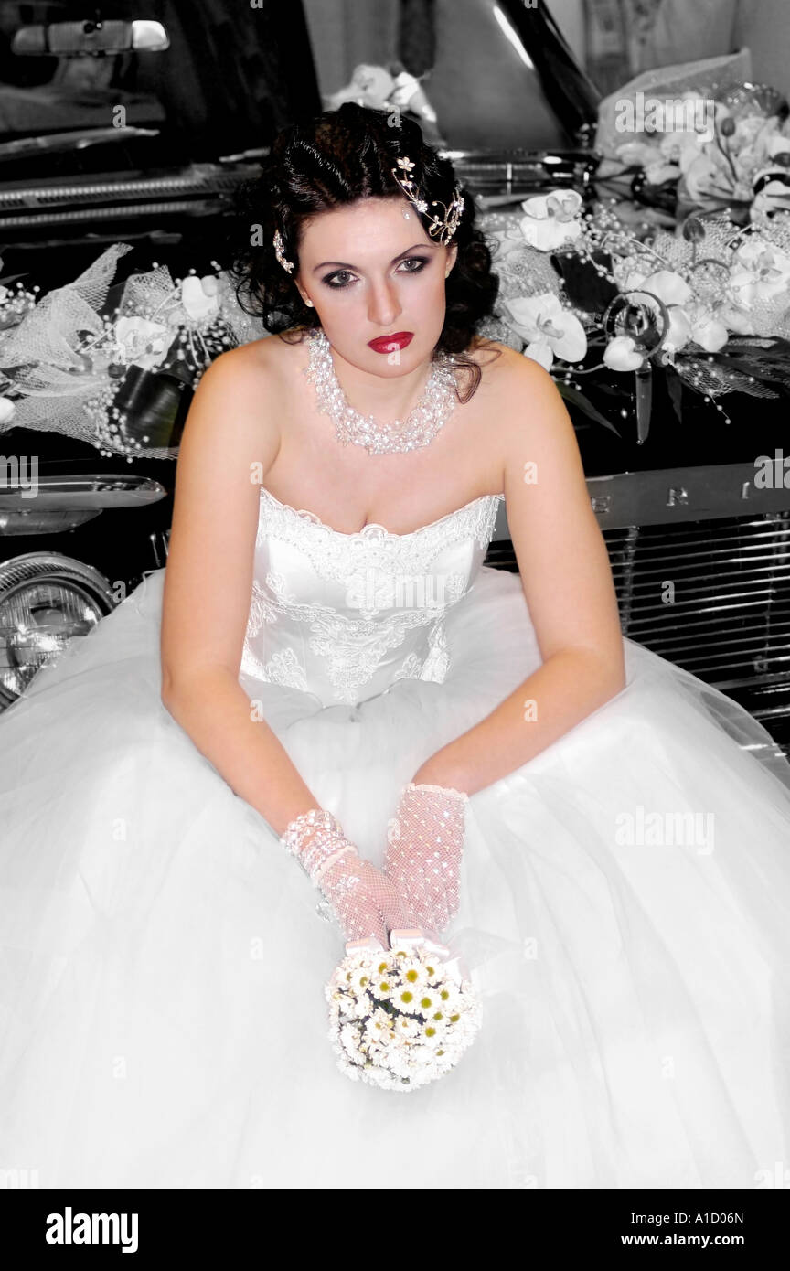 Lonely Bride Young woman in wedding gown siting on a car Stock Photo