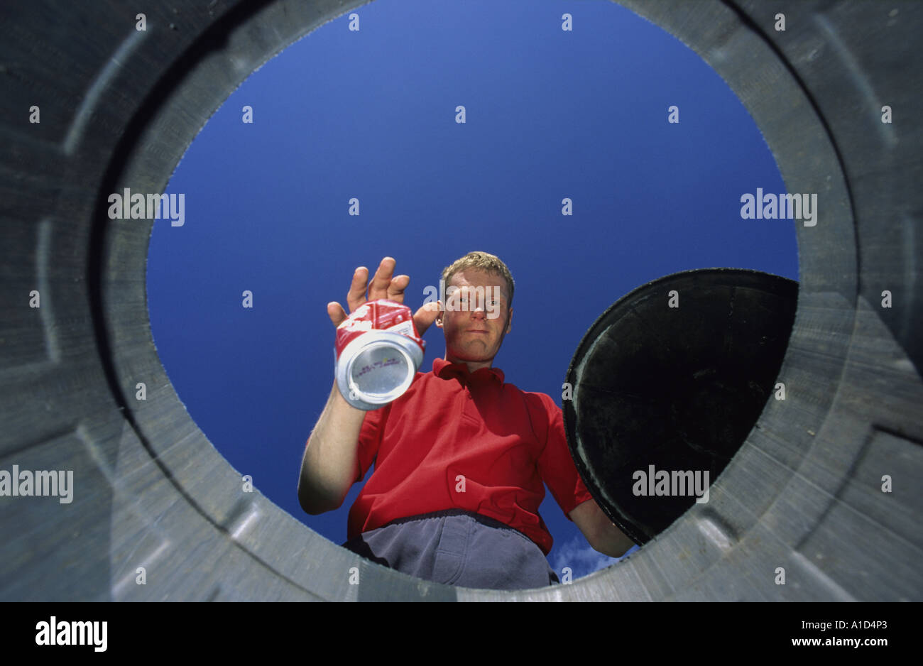 man throwing recyclable aluminium can into recycling bin uk Stock Photo