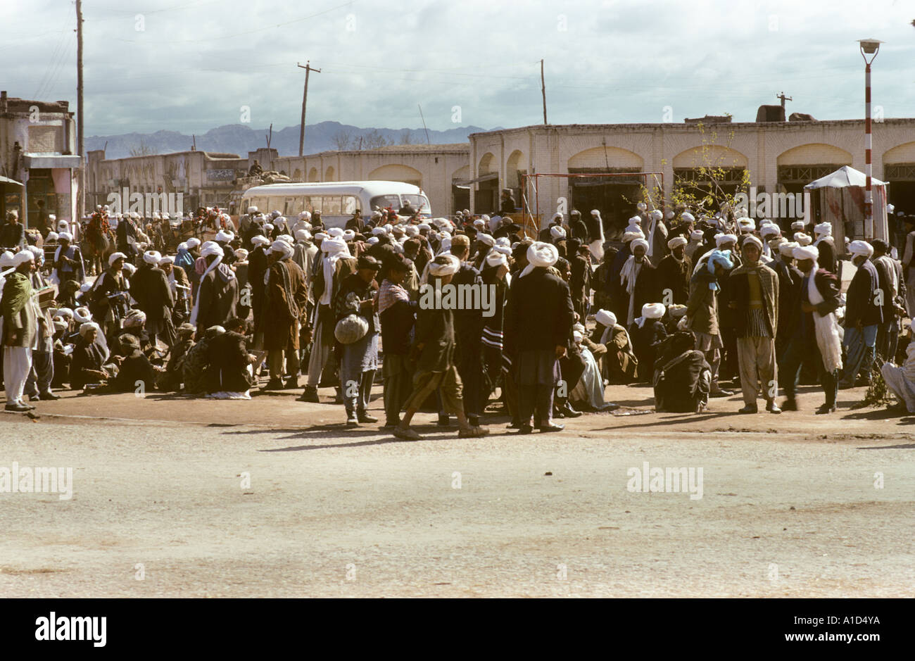 town square men gathering to wait for transport bus lorry coach wagon depot terminus - Stock Image