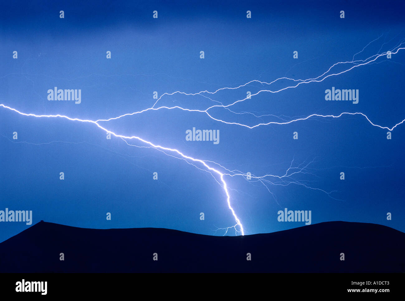 Lightning strike above a mountain top fire-lookout cabin - Stock Image