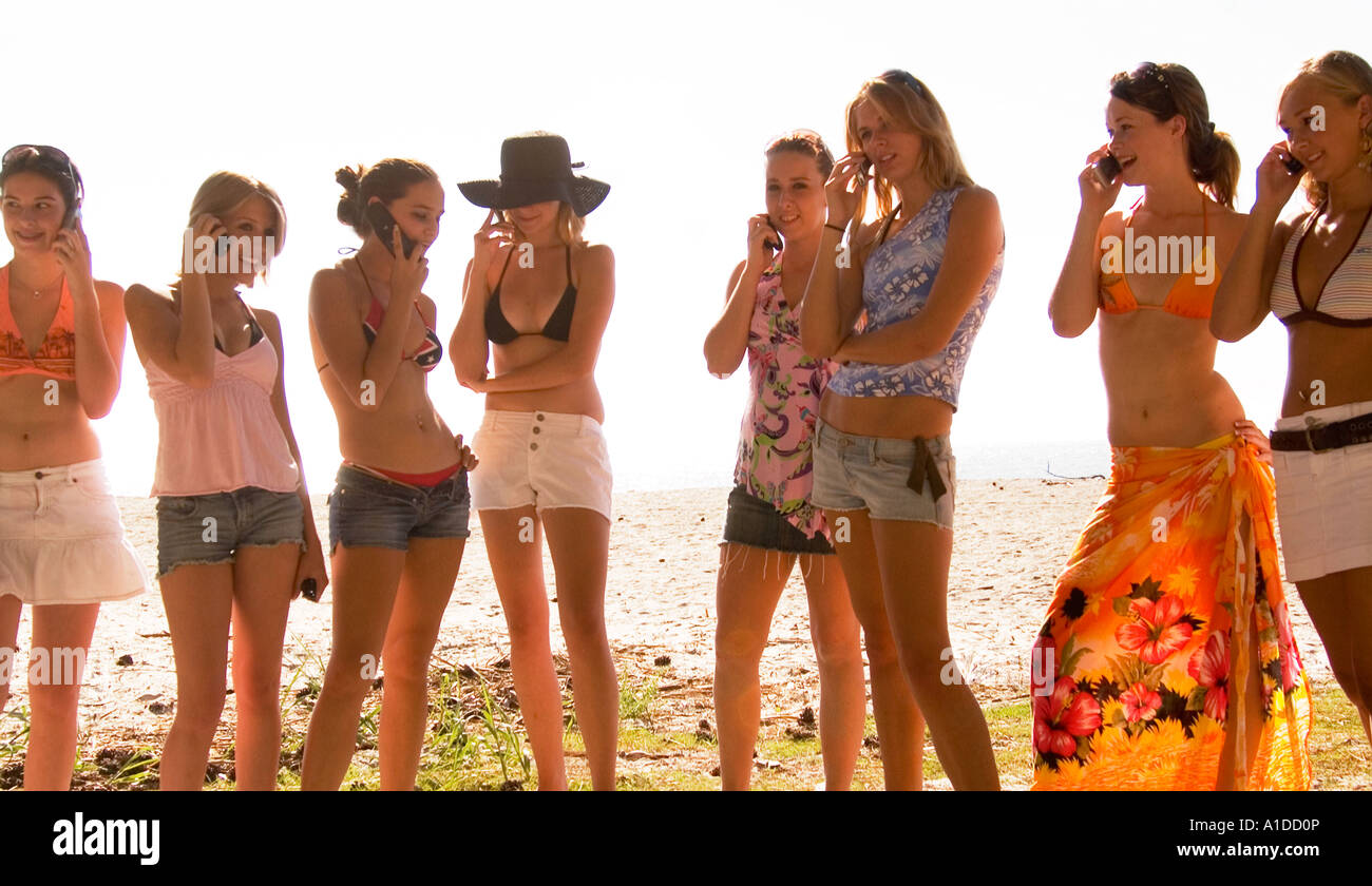 Eight Caucasian Teen Girls Talking on Cellphones at Hunting Island Beach USA, Communications and Vacation Stock Photo