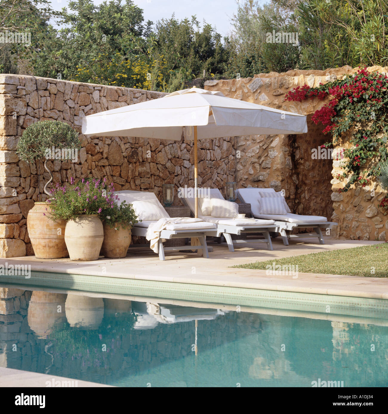 Sun loungers by swimming pool - Stock Image