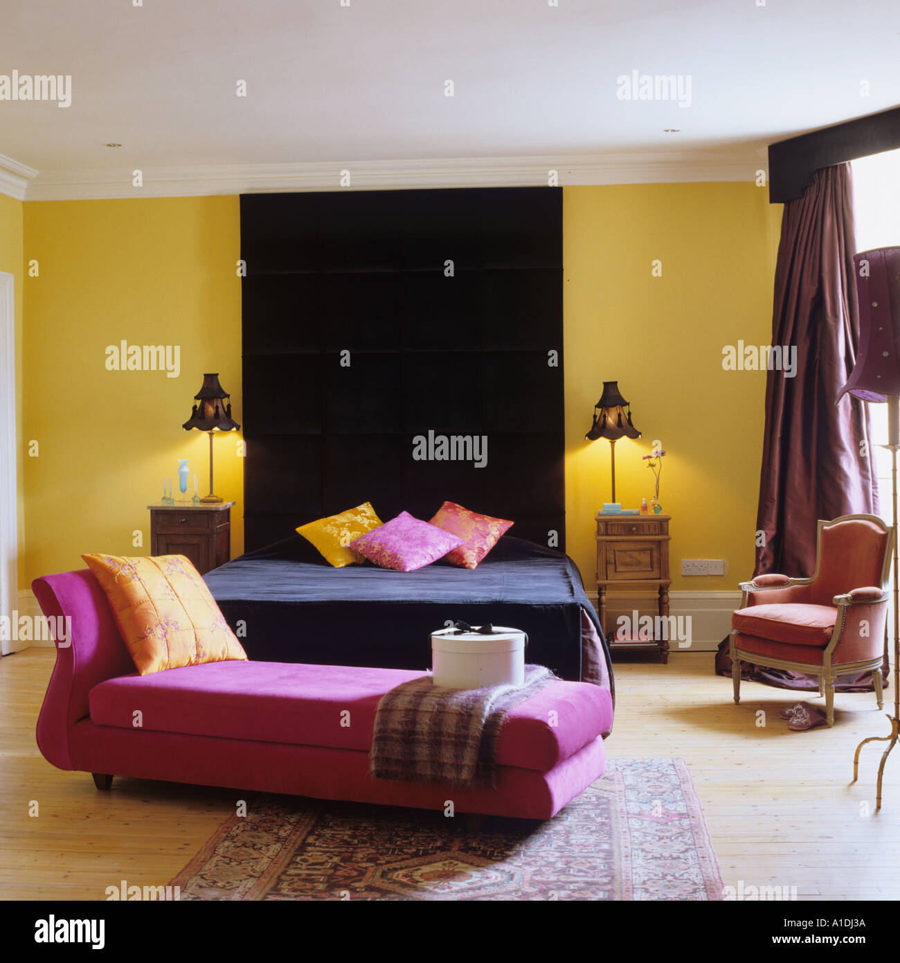 Pink chaise longue and black bed in yellow bedroom Stock ...