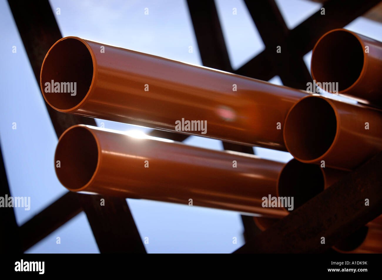 LENGTHS OF UNDERGROUND SOIL OR DRAINAGE PIPES ON A RACK IN A BUILDERS YARD - Stock Image