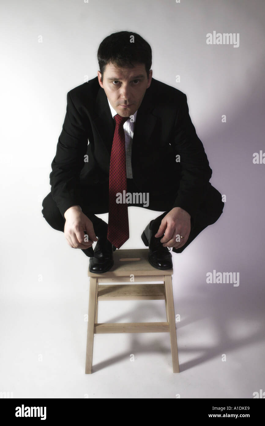 Business man crouches on a stool looking forward with a focused air - Stock Image