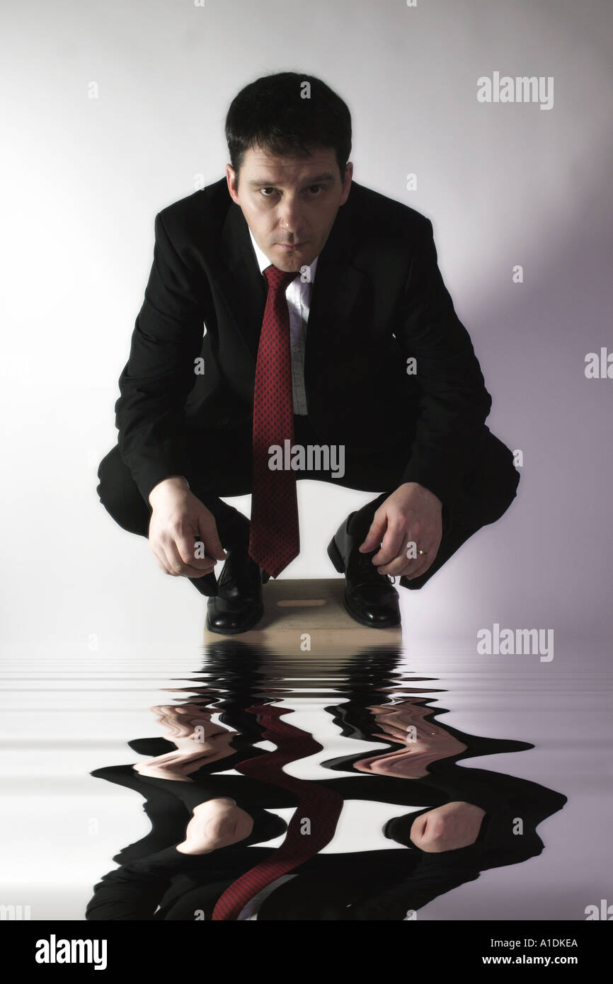 Business man crouches on a stool looking forward with a focused air over water dealing with a crisis - Stock Image