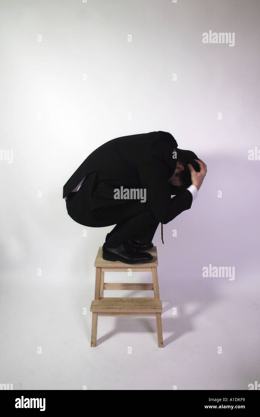 Man in suit crouching on top of a stool - Stock Image
