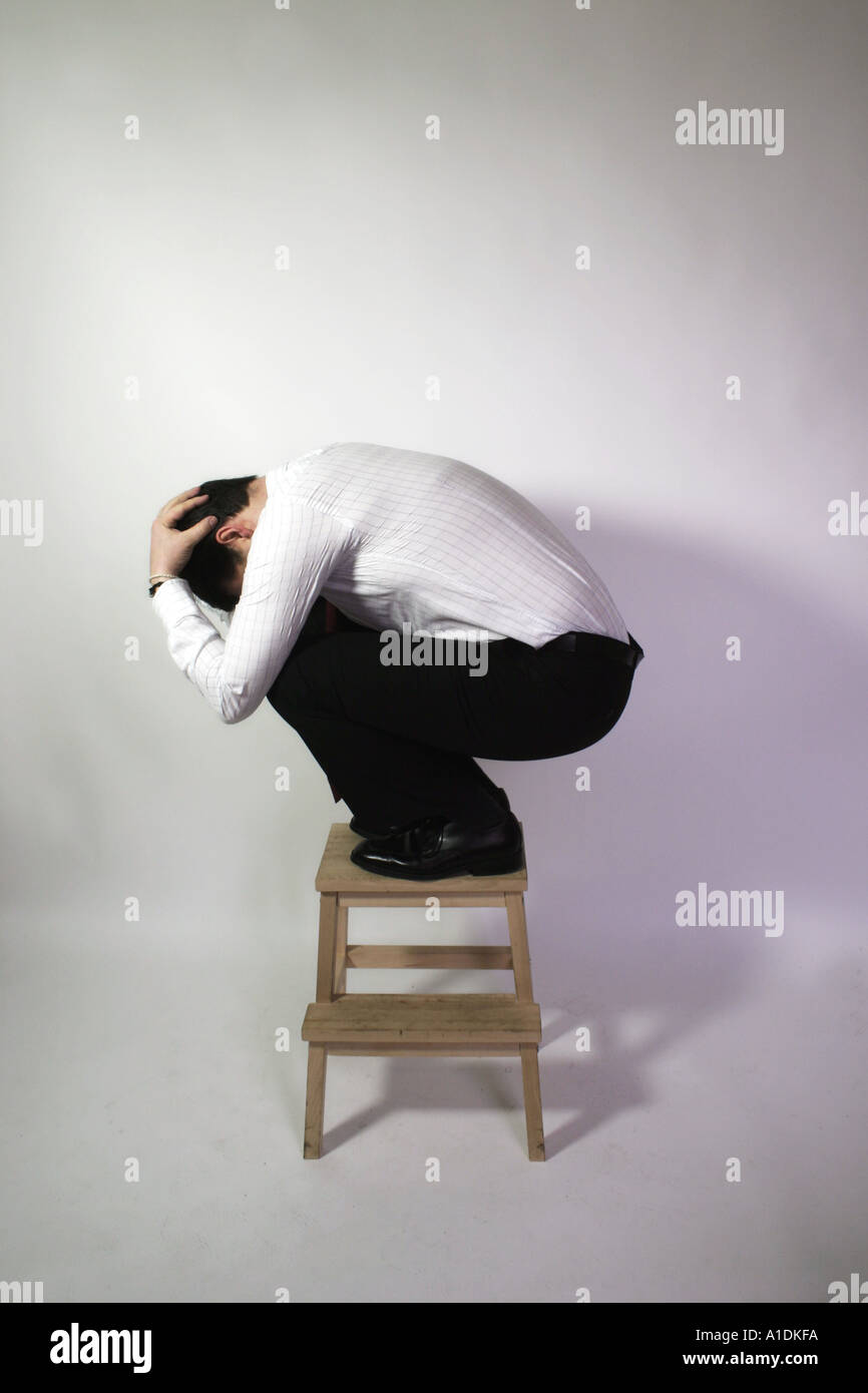 Man in shirt and tie crouching on top of a stool - Stock Image