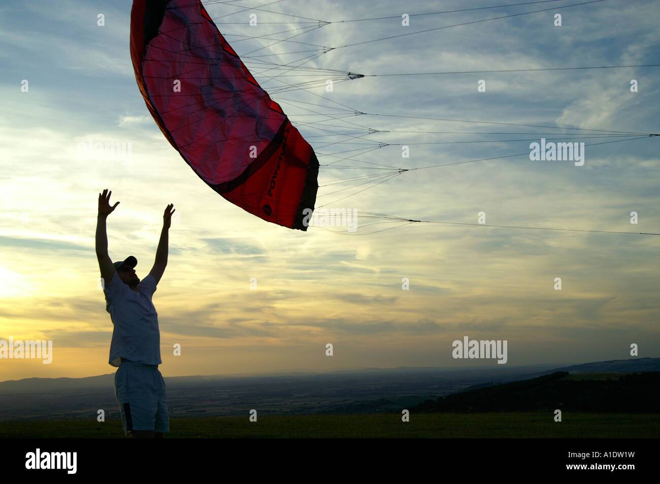 Man teenage boy starting parachute powerkite kite on meadow hill over evening colourful sky outdoors - Stock Image
