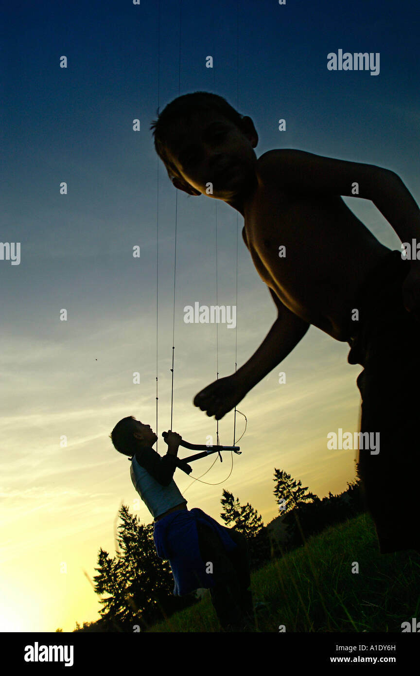 Two small kid child flying parafoil powerkite in twilight silhouette colourful sky outdoors evening summer - Stock Image