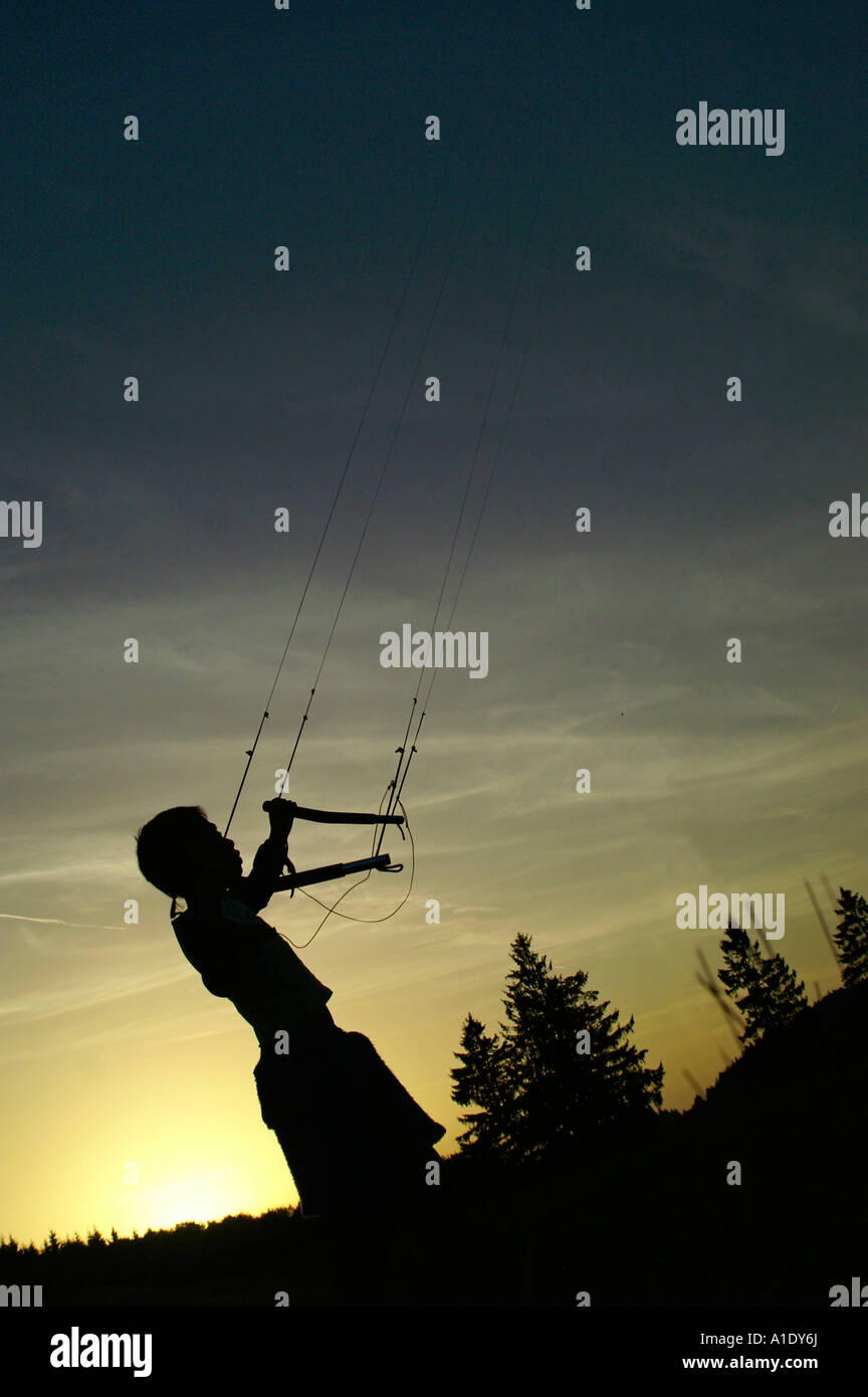 One small kid child flying parafoil powerkite in twilight silhouette colourful sky outdoors evening summer - Stock Image