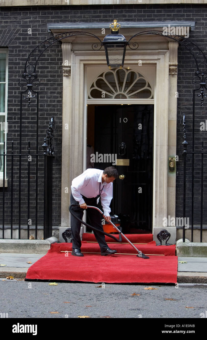 Cleaner hoovers the carpet outside Number 10 Downing Street the home of the British Prime Minister London United Kingdom - Stock Image