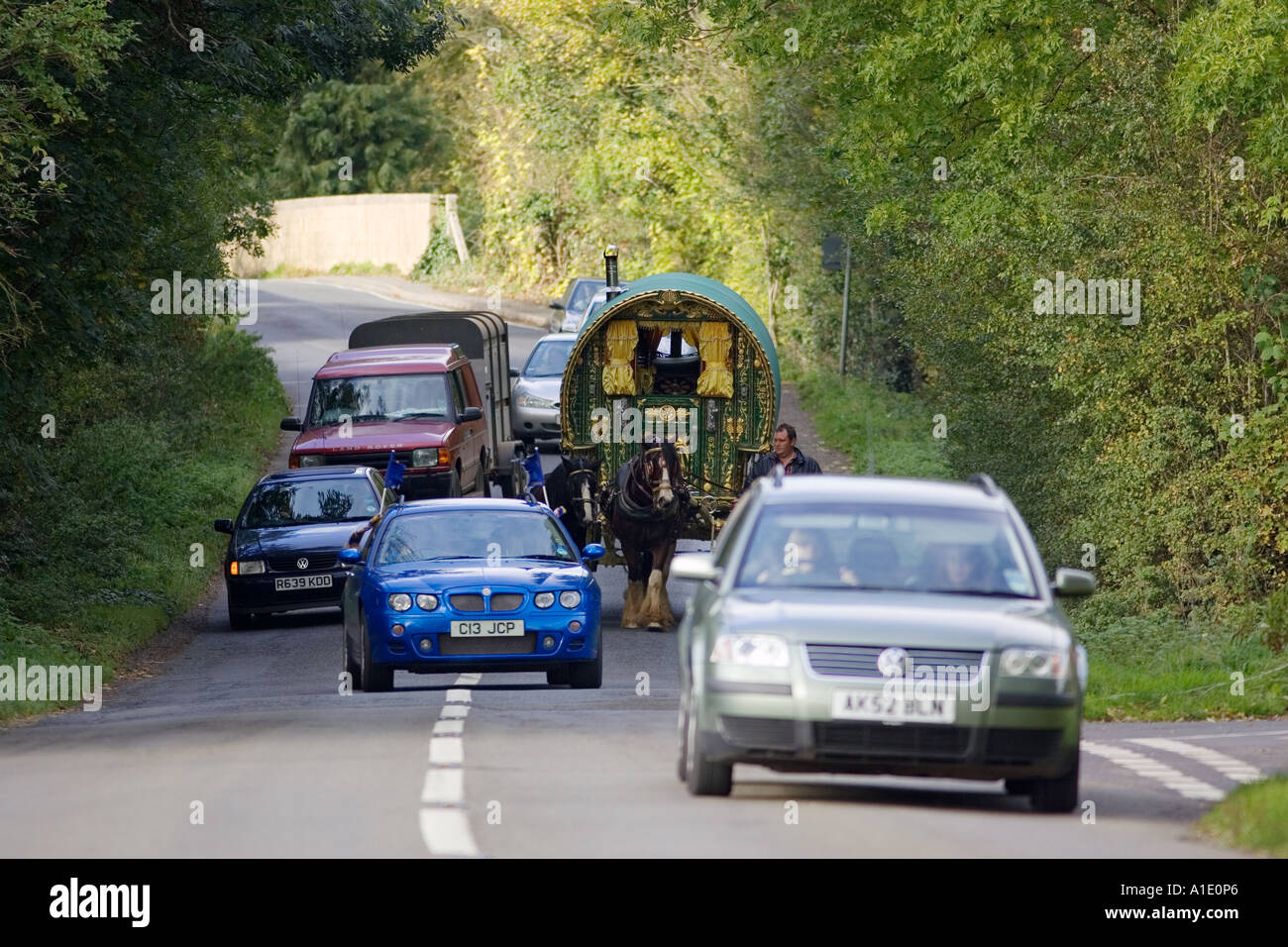 Cars overtake shire horse drawn gypsy caravan on country lanes Stow On The Wold Gloucestershire United Kingdom Stock Photo