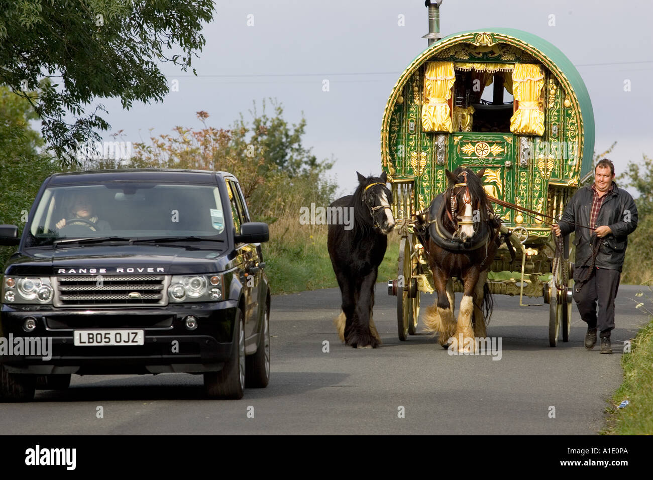 Range Rover car overtakes shire horse drawn gypsy caravan on country lane Stow On The Wold Gloucestershire United Kingdom - Stock Image