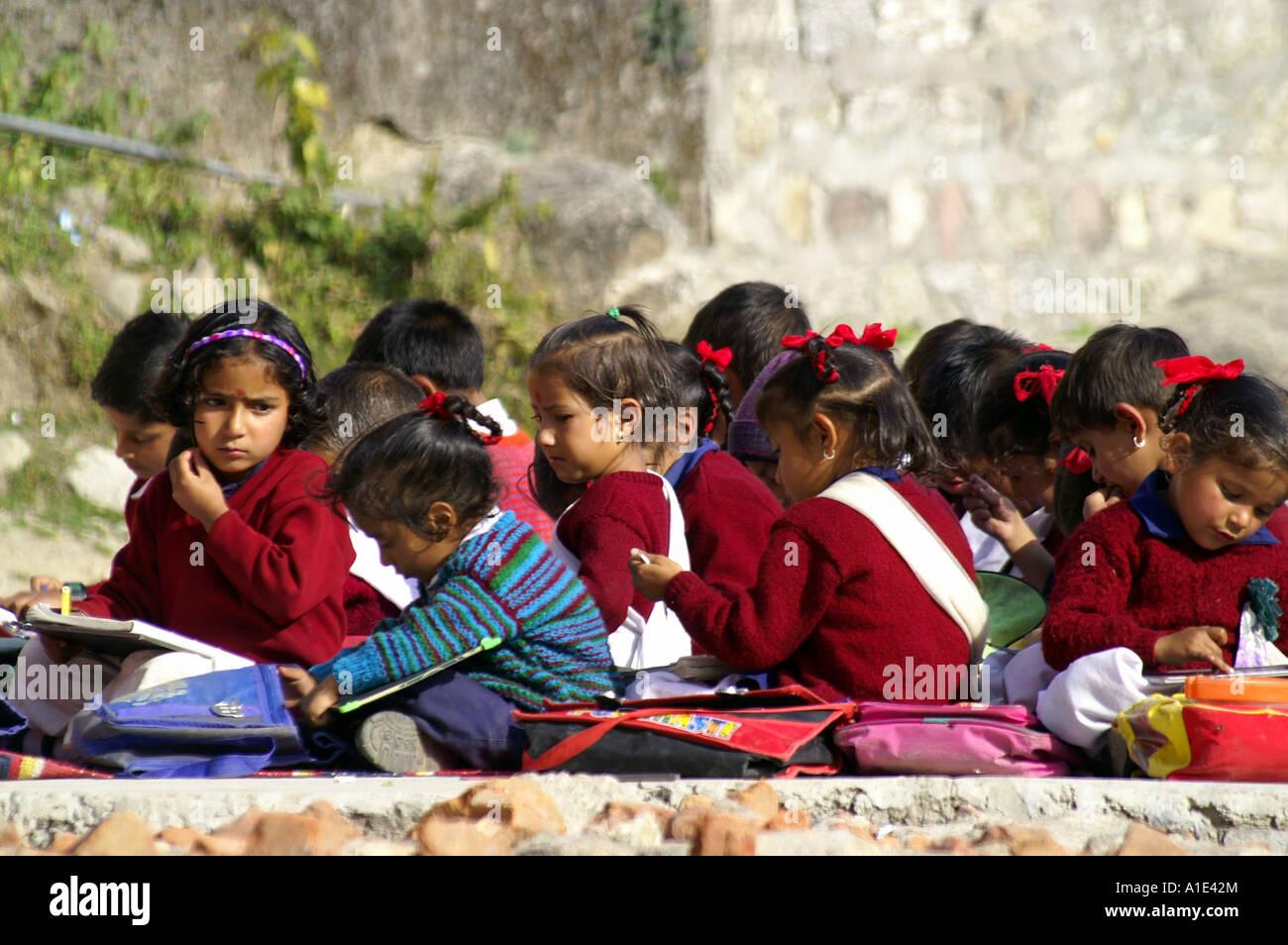 Group of young children schoolboys schoolgirls indian kids sitting writting exam outdoors school yard, Bhagsunag, - Stock Image