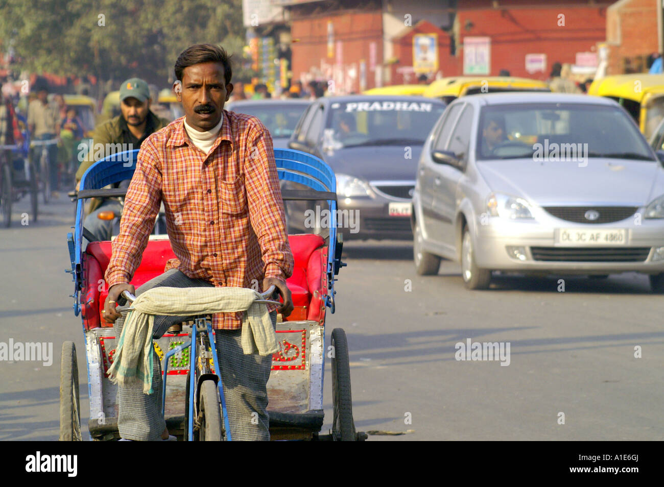 Rickshaw bicycle and modern cars - changing India trasport, street of New Delhi Stock Photo