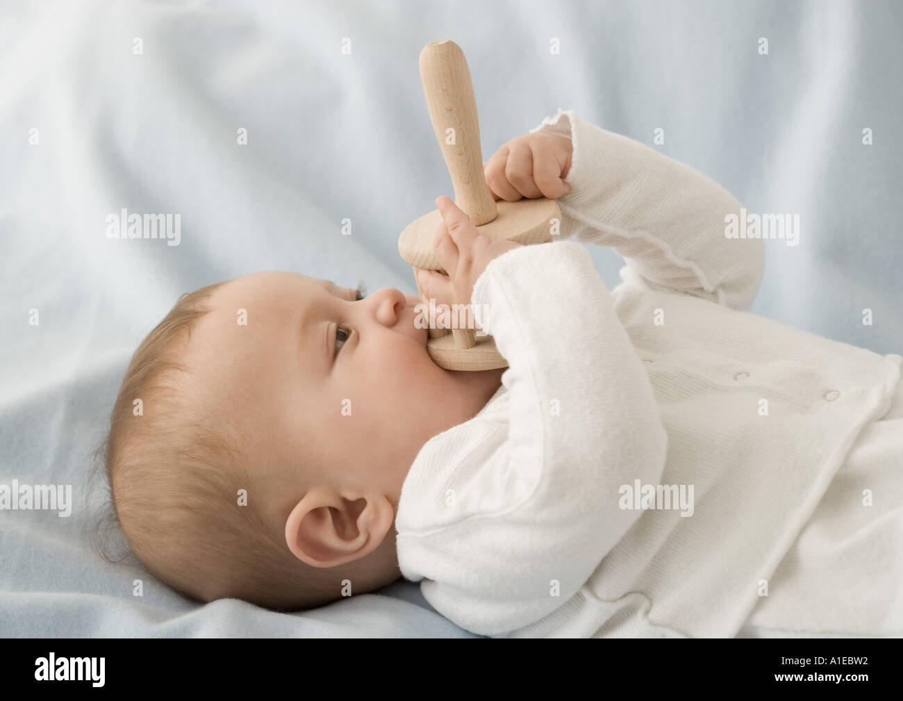 Baby chewing on rattle - Stock Image
