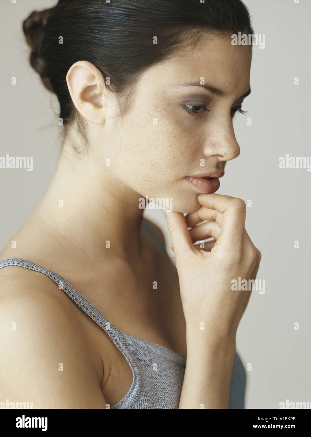 Woman with hand under chin, portrait - Stock Image