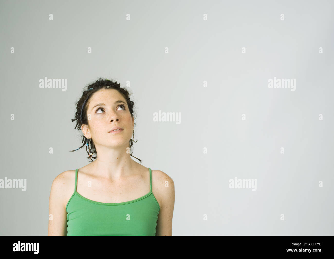 Young woman wearing tank top looking up - Stock Image