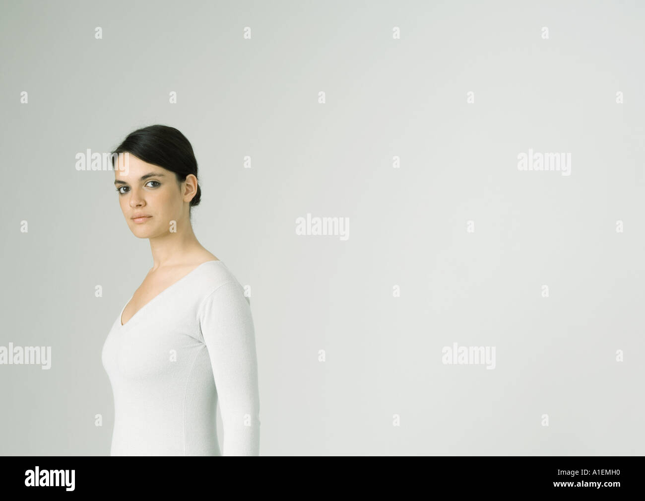 Young woman standing, looking at camera - Stock Image