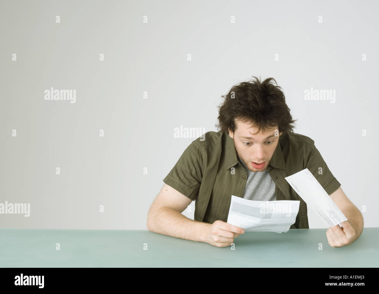 Young man looking at letter, reacting with surprise - Stock Image
