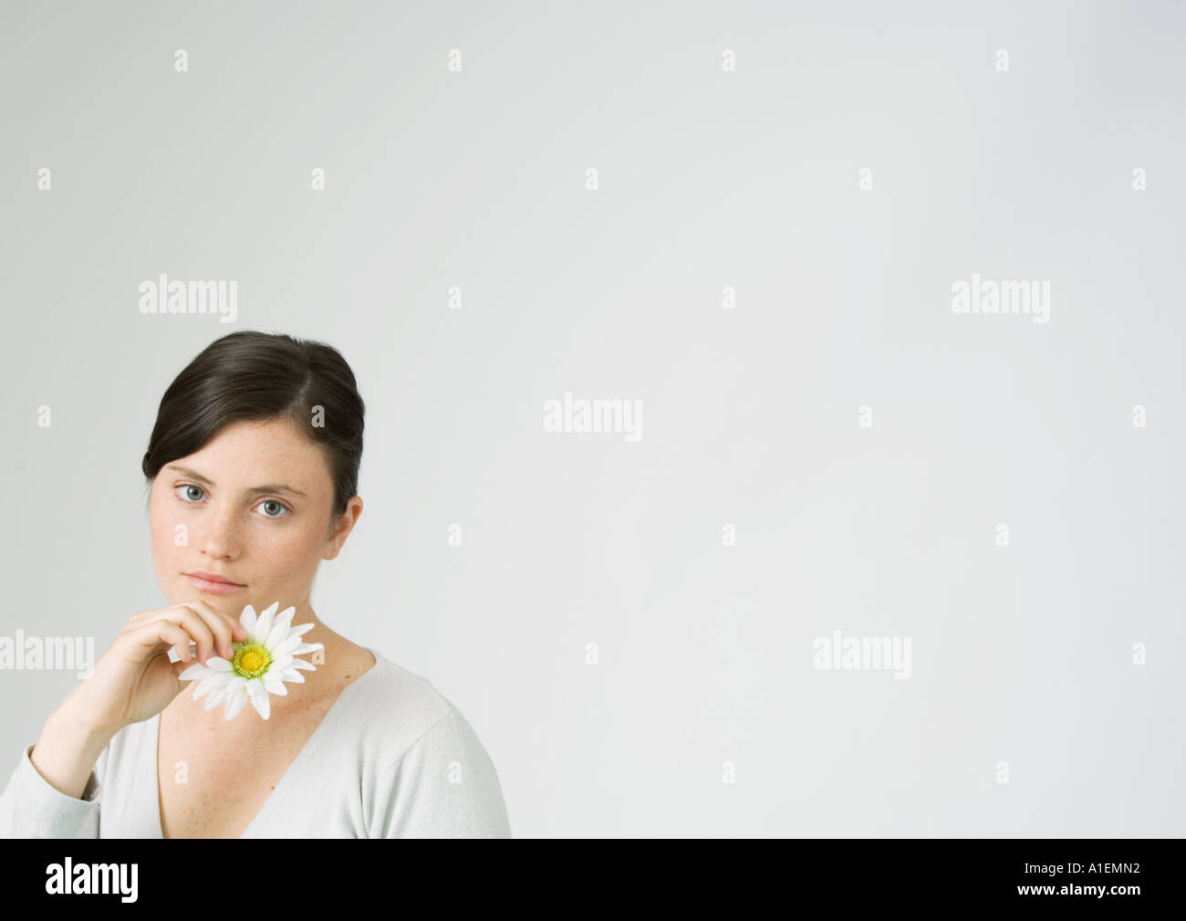 Young woman holding daisy - Stock Image