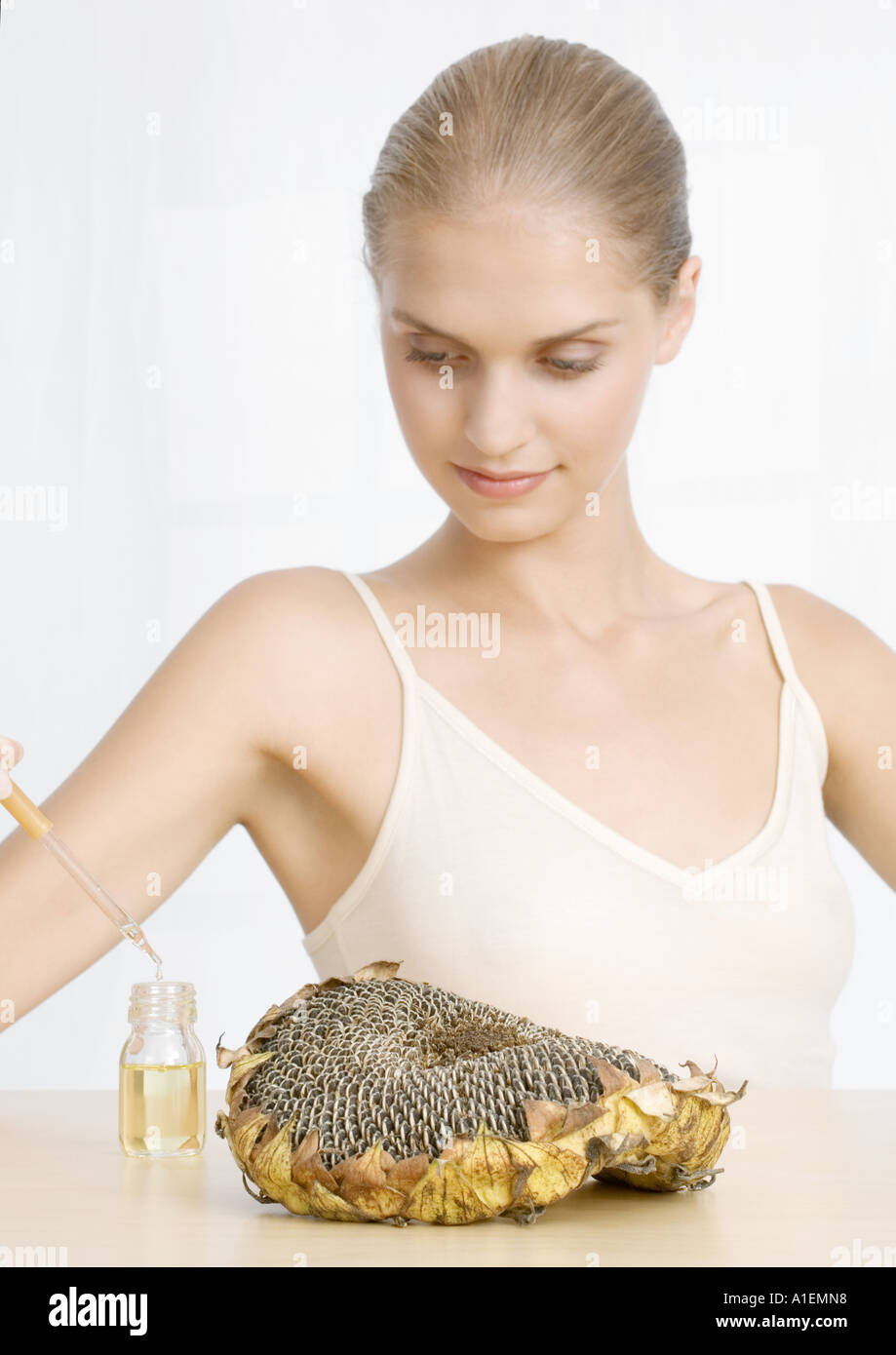 Woman with dried sunflower head and essential oil - Stock Image