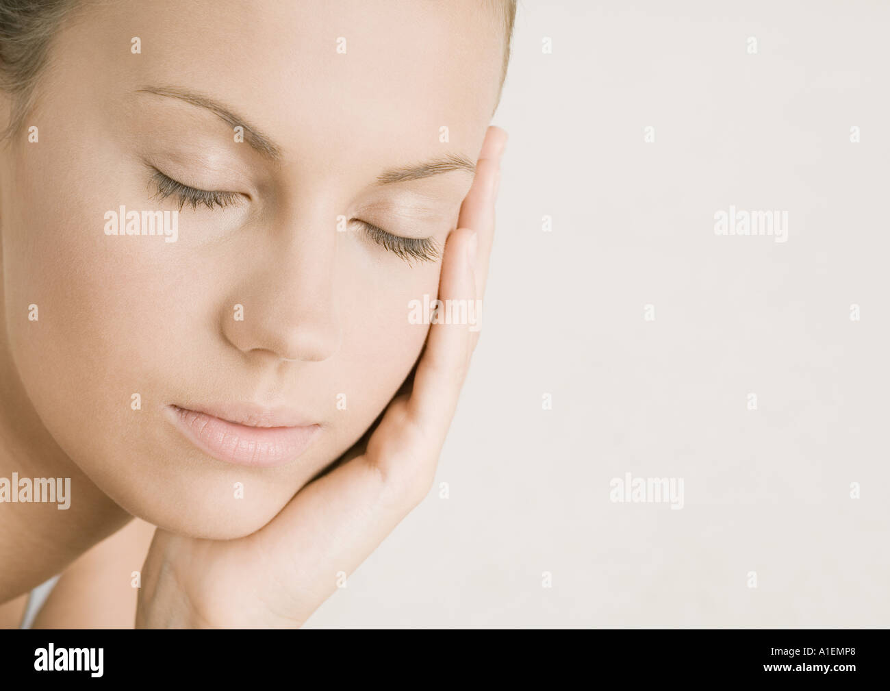 Young woman with eyes closed resting head on hand - Stock Image