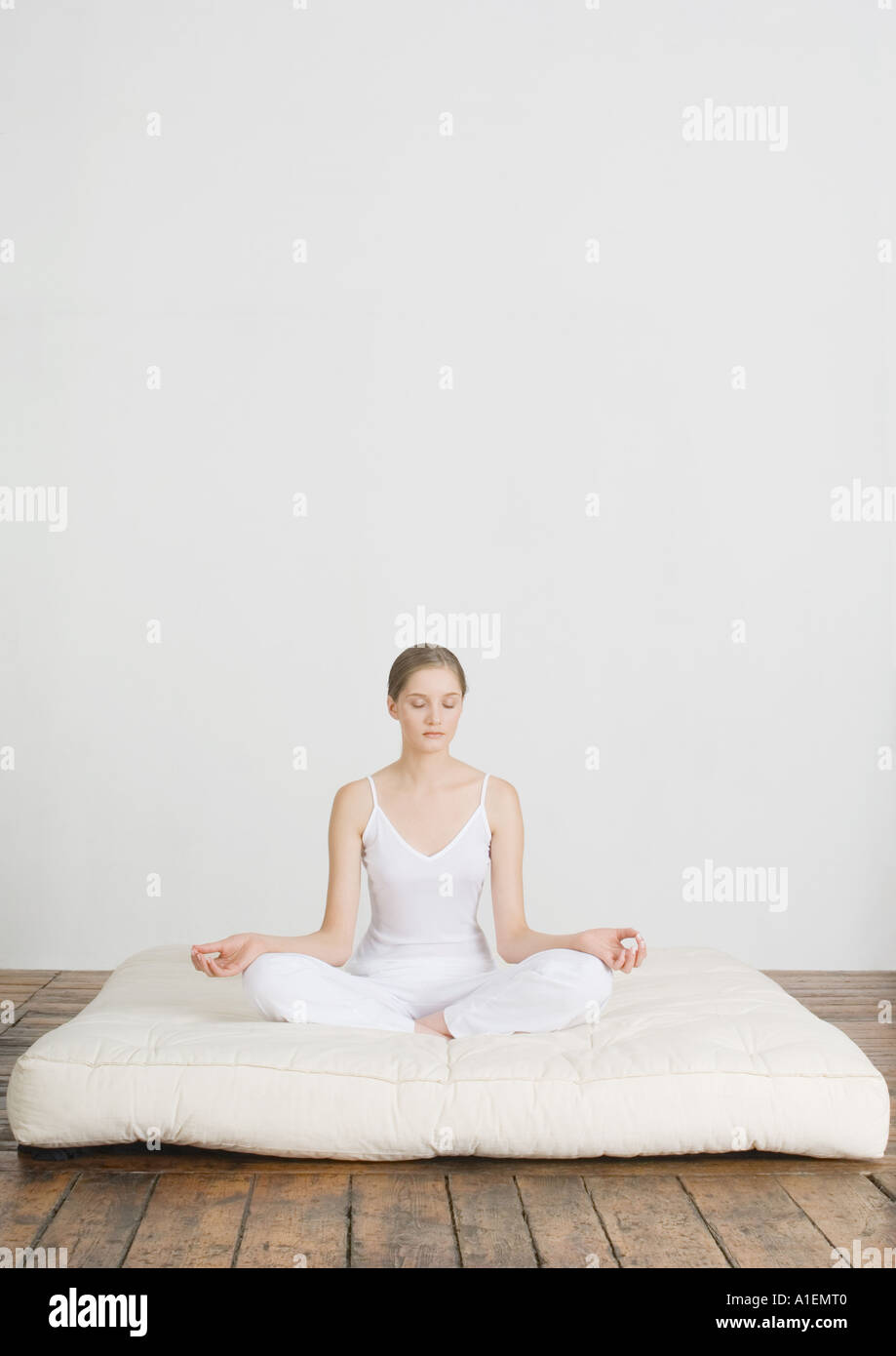 Young woman sitting in lotus position on futon mattress - Stock Image