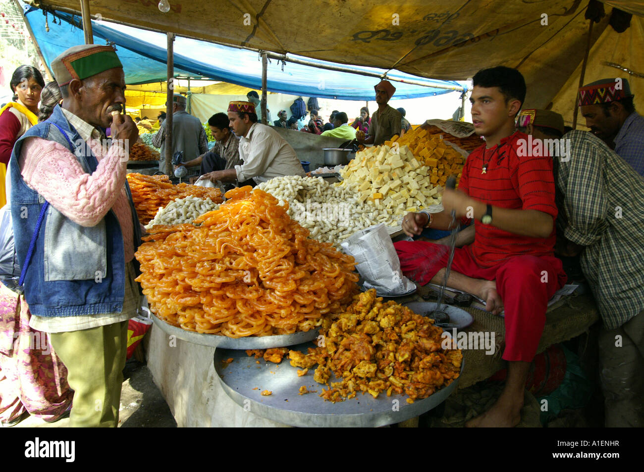Man weighing sweets at Dussehra fair with enormous variety of rich Indian cuisine meals, Kullu, India - Stock Image