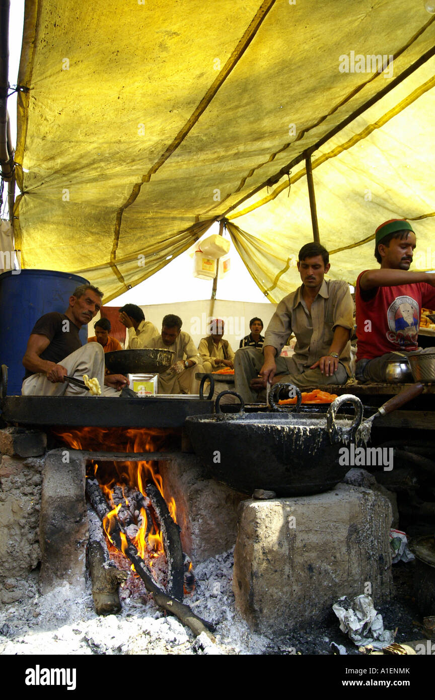 Man frying sweets at Dussehra fair with enormous variety of rich Indian cuisine meals, Kullu, India - Stock Image