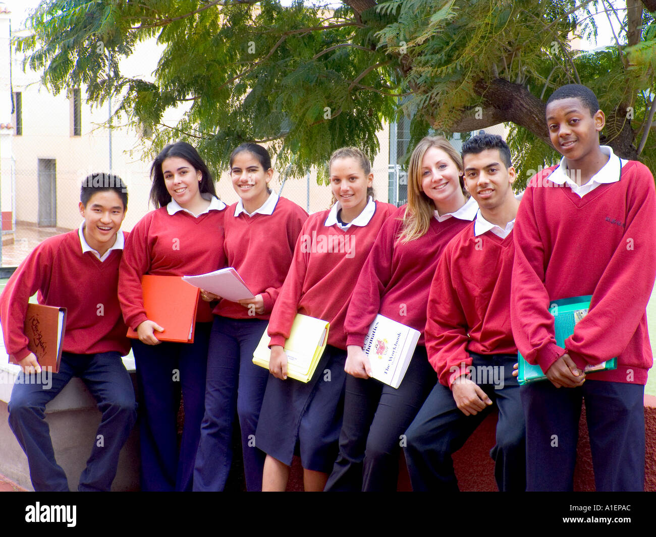 Multiracial group of happy teenage students outside in school playground - Stock Image
