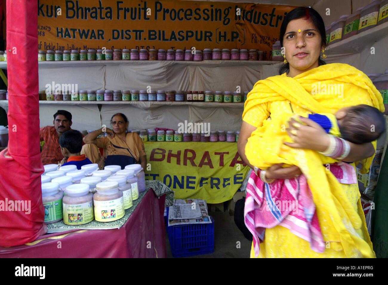 Indian woman in yellow sari holding her kid in shop with processed food, Kullu, India - Stock Image