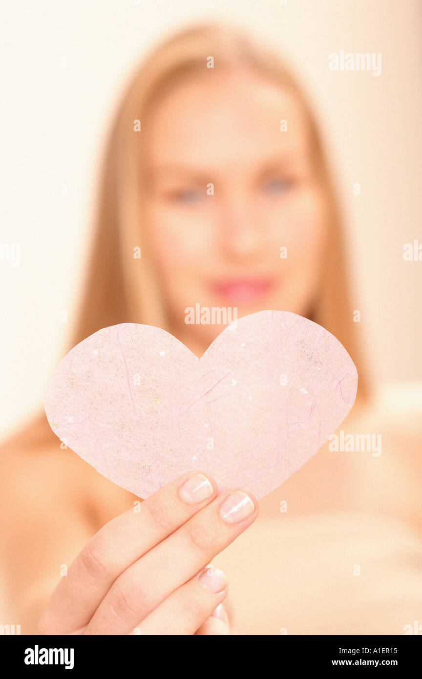 Woman holding pink heart - Stock Image