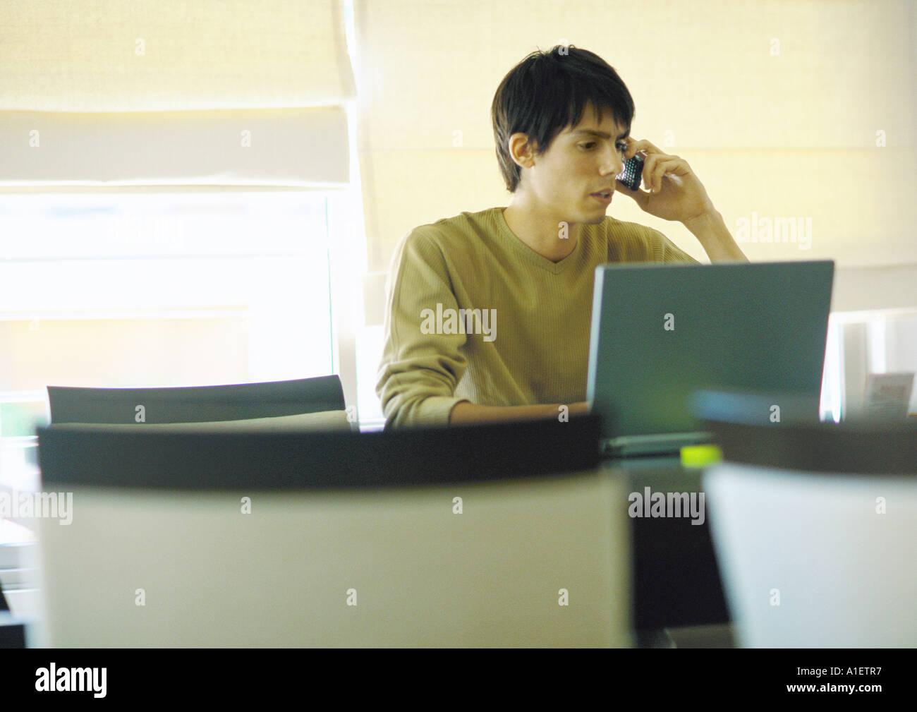 Man using laptop and phoning - Stock Image