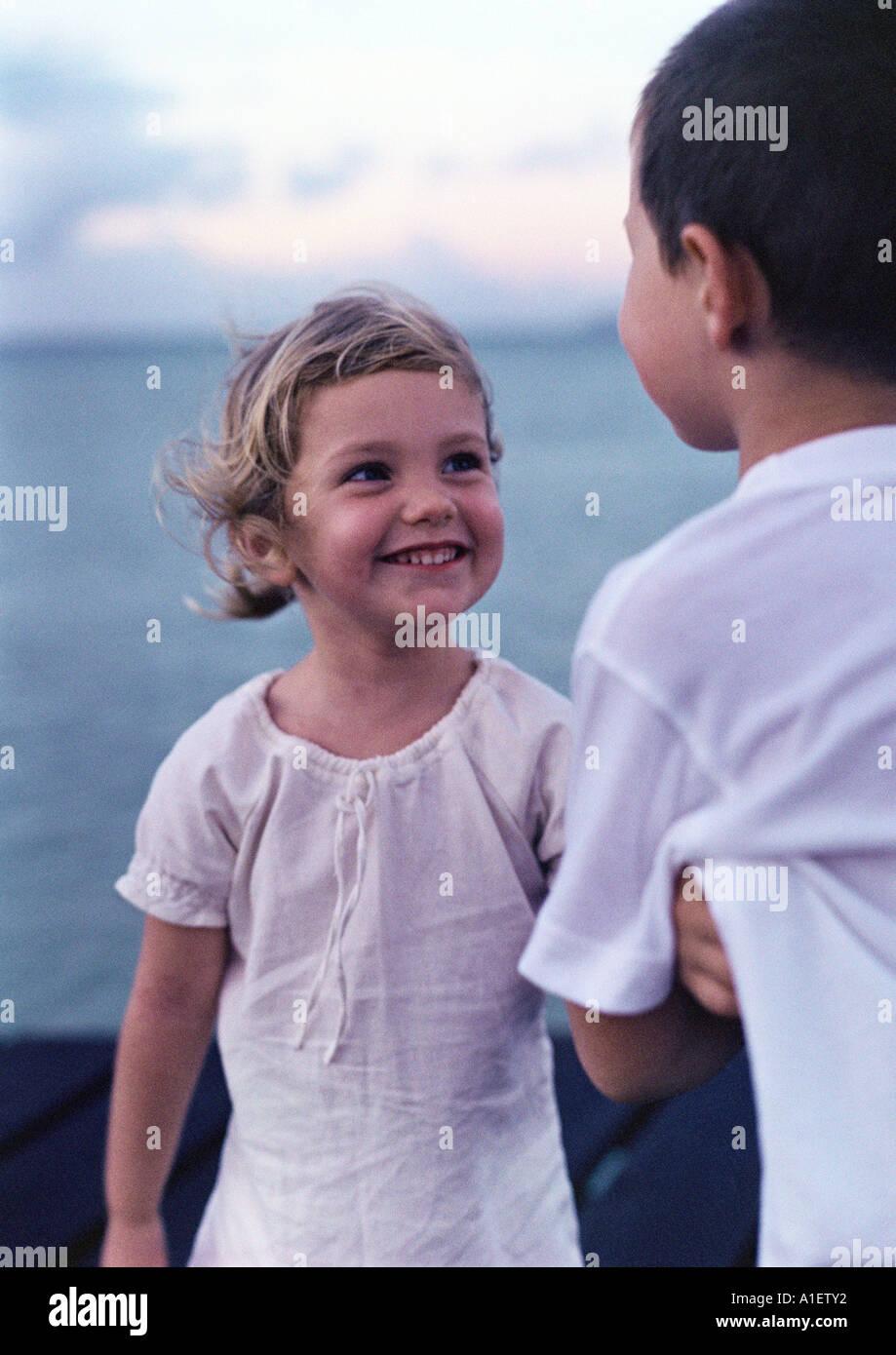 Girl smiling at boy near sea - Stock Image