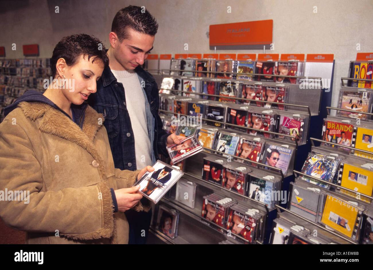 Young people shopping for CD s in an Italian music store  - Stock Image