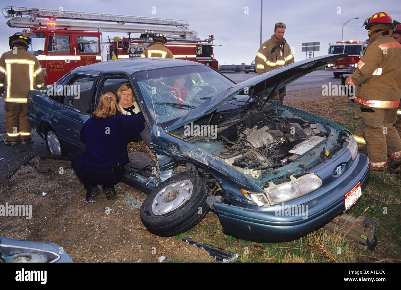 Firefighters assist in the aftermath of an automobile accident  - Stock Image