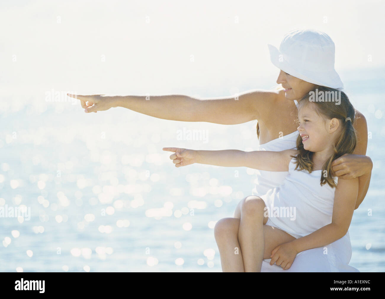 Mother and daughter pointing in front of sea - Stock Image