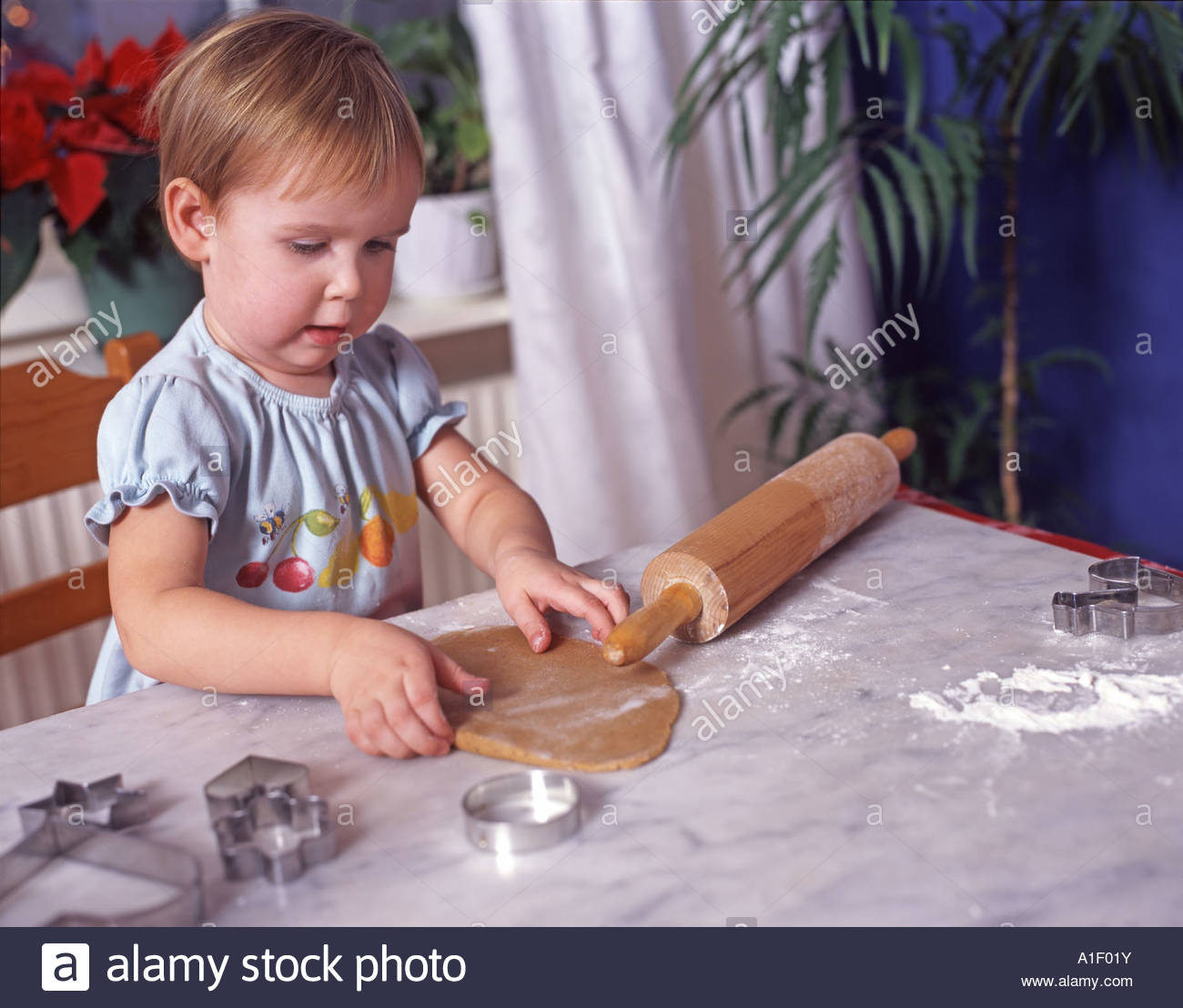 Two year old girl baking gingerbread at Christmastime - Stock Image