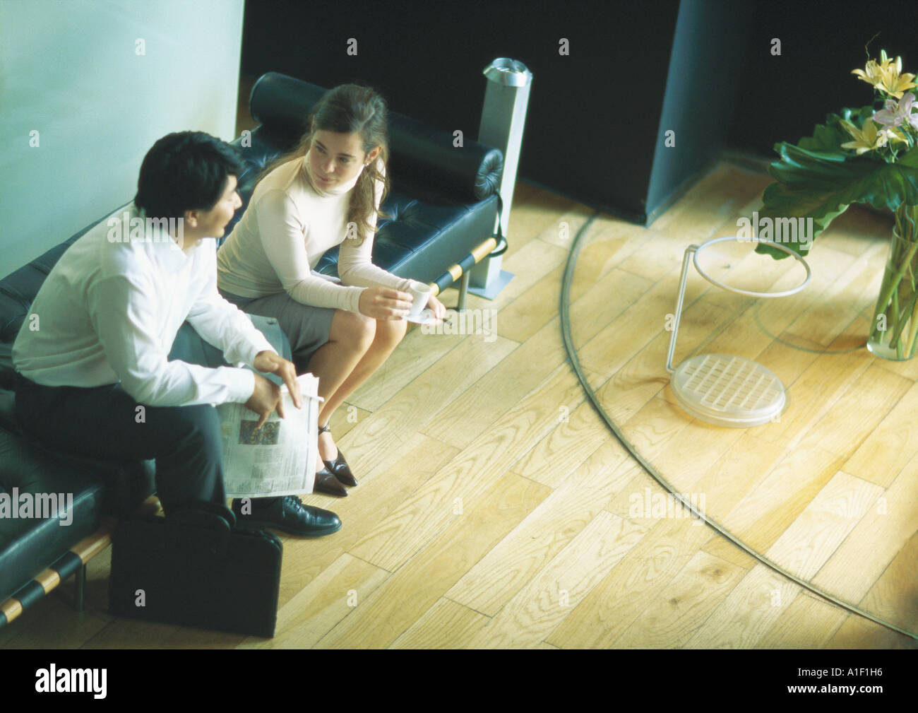 Man and woman sitting on bench in lobby, high angle view - Stock Image