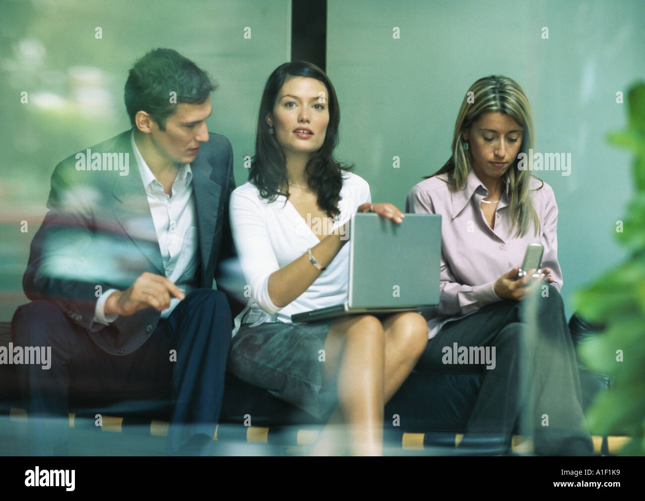Businesswoman sitting between co-workers, looking up from laptop - Stock Image