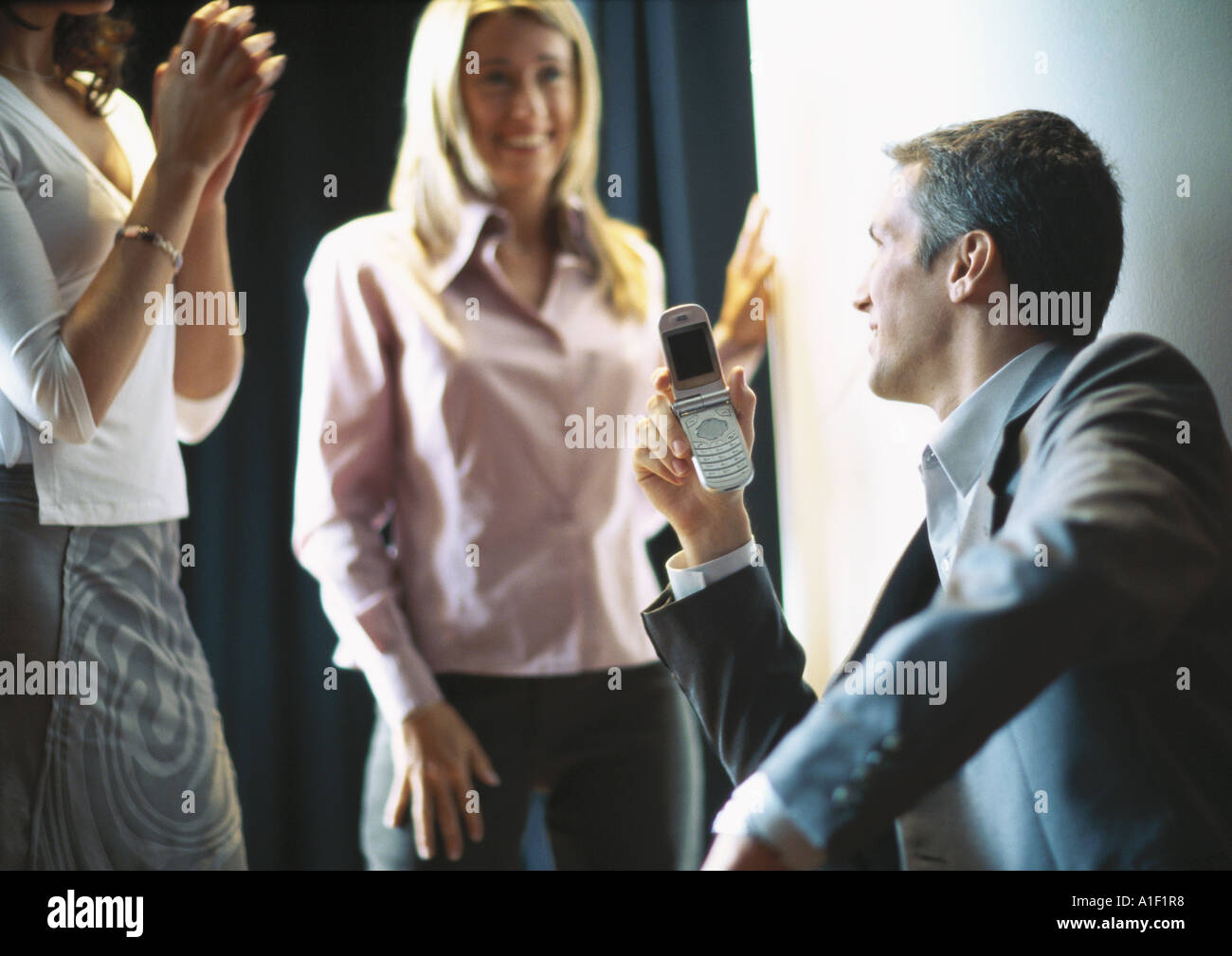 Businessman holding up cellphone, female colleagues smiling and clapping - Stock Image