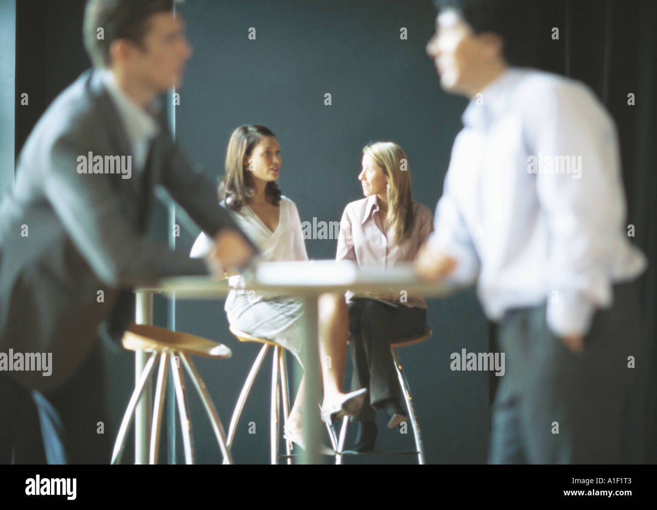 Businesspeople talking in cafe setting - Stock Image