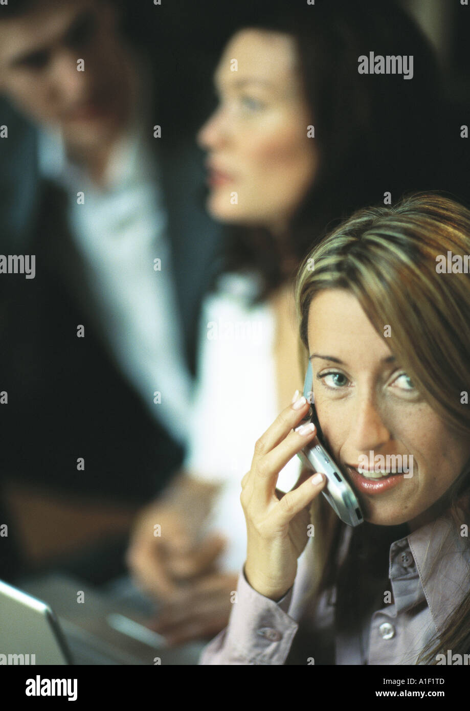 Businesswoman using cell phone in front of two co-workers - Stock Image
