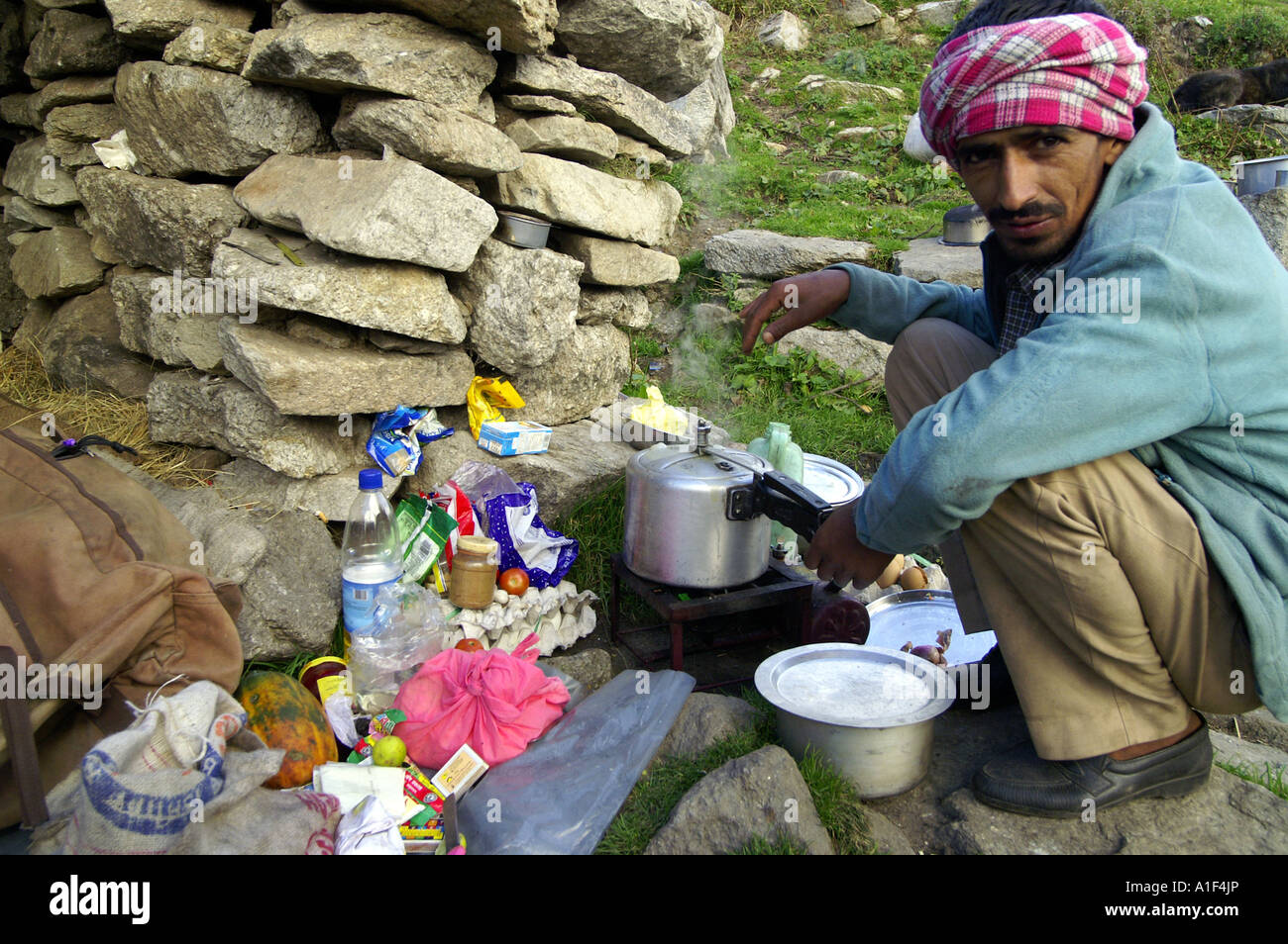 Indian man cooking outdoors in pressure cooker - Stock Image
