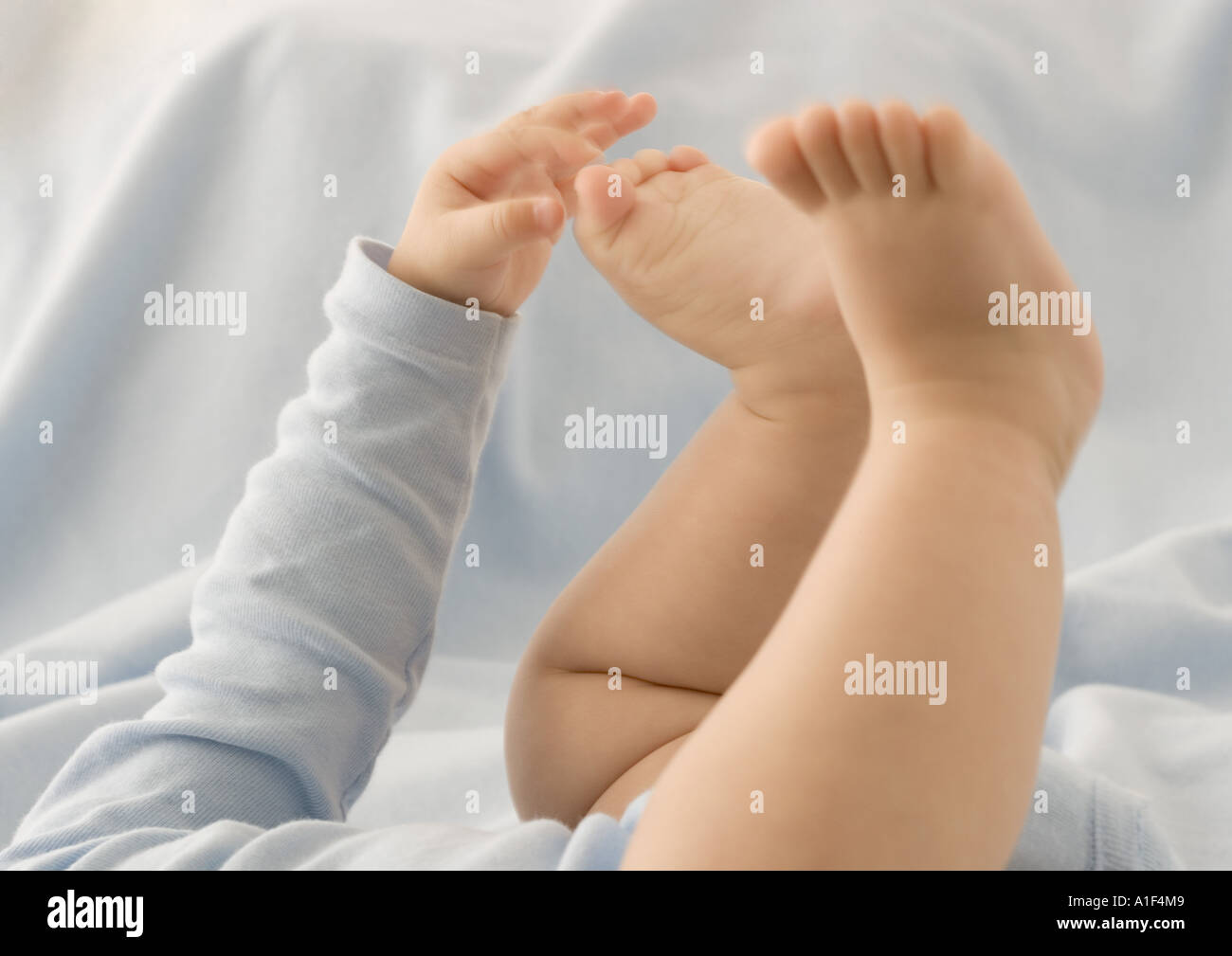 Baby touching toes, cropped view Stock Photo