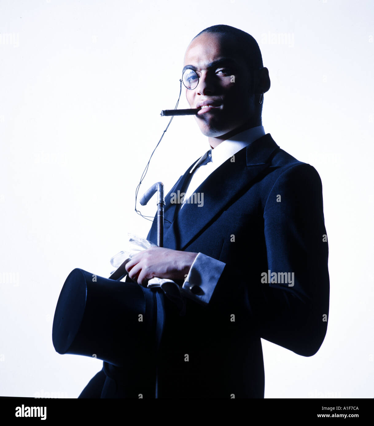 Young black man with monocle, cigar and tailcoat outfit looking very self-confident in to the camera - Stock Image