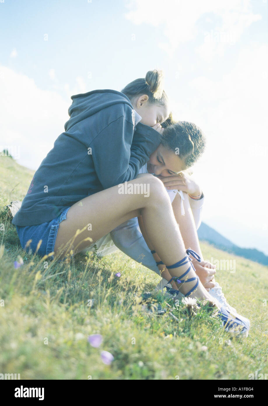 Two girls whispering and sitting on grass together - Stock Image