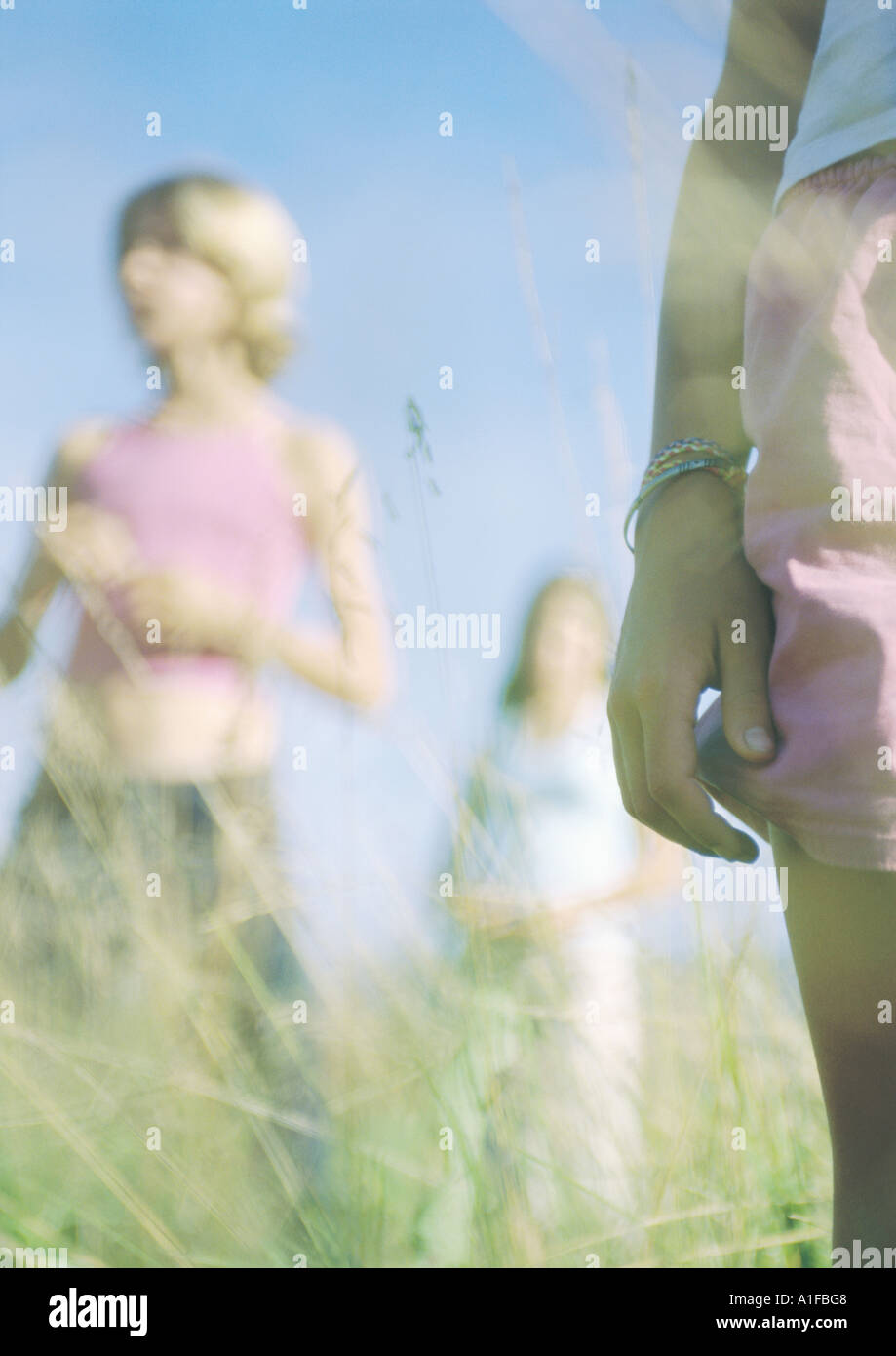Three youngsters standing in grass - Stock Image